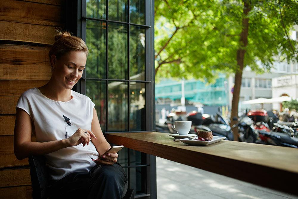 Woman looking at phone at coffee shop