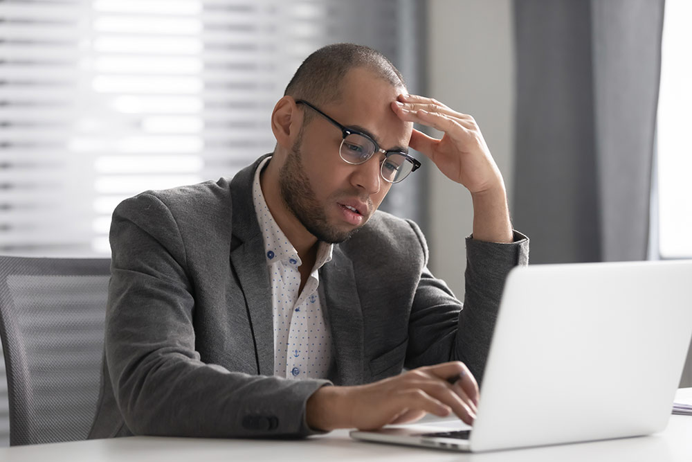 Man frustrated and upset looking at laptop with hand on forehead