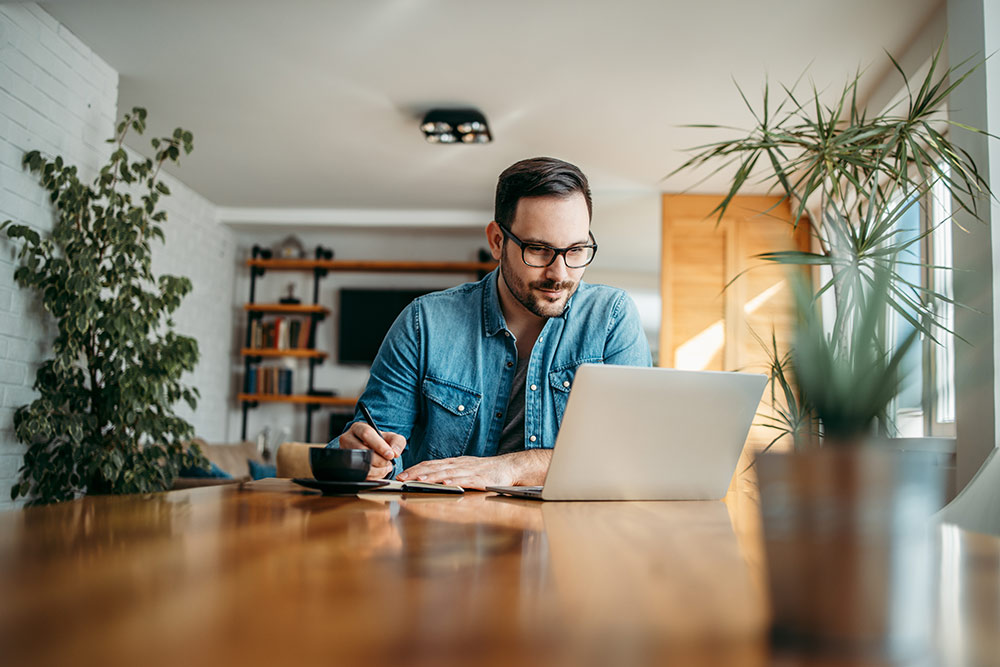 Man working on laptop at table, working on website
