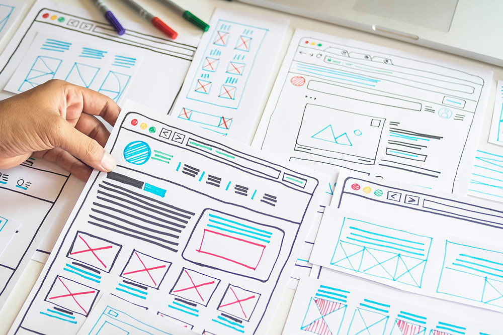 Papers spread out with website design layout sketched on them