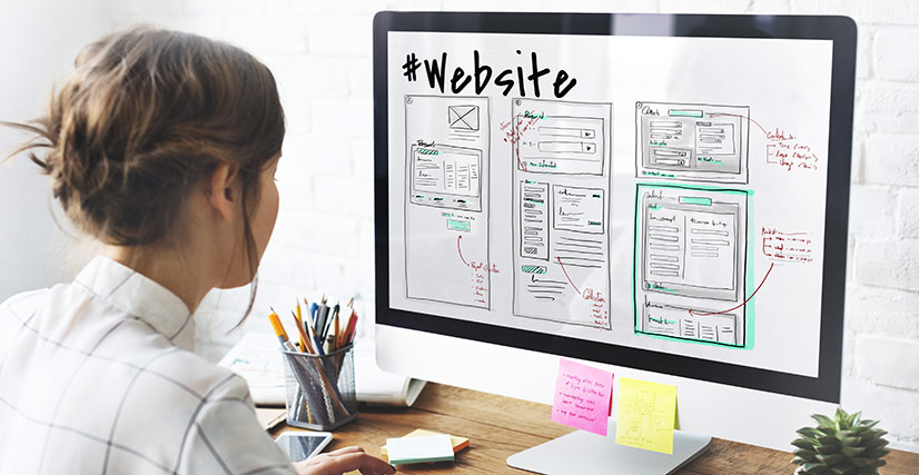 Woman sitting at desktop computer working on website design layout