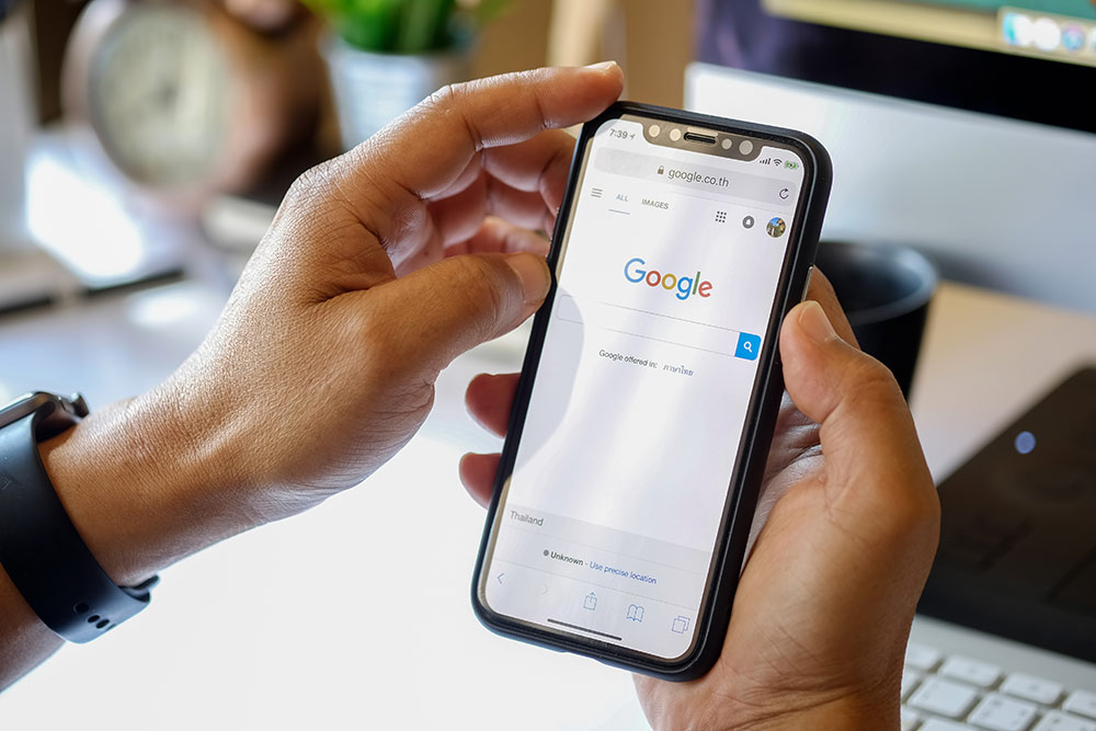 Close up of someone holding phone doing a search on Google