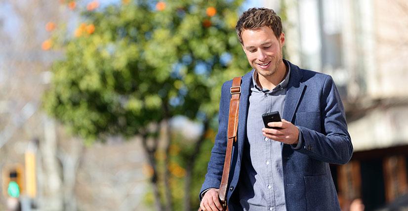 Man walking outside, looking down at phone smiling