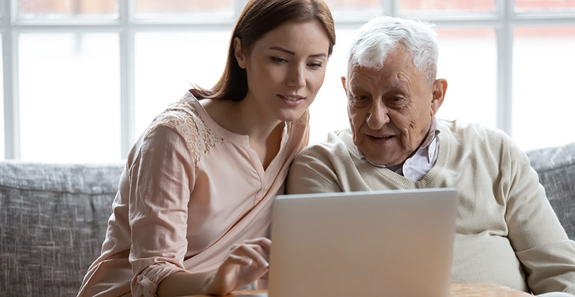Woman sitting with senior father on couch on laptop