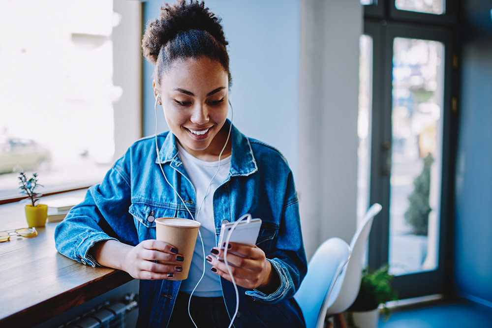 Woman sitting in coffee shop holding coffee while holding smartphone with headphones in, smiling at phone