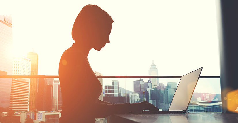 Woman sitting at table on laptop with city skyline in background