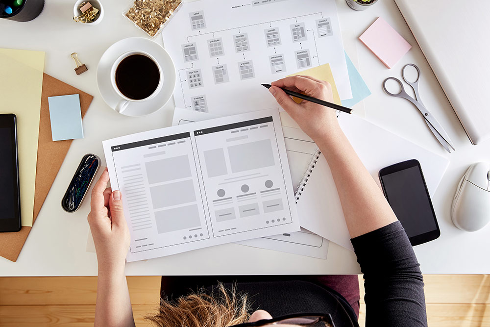 Person sitting at desk working on web design wireframe